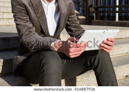 Businessman resting from work and while sending messages and talking with his white tablet. He is sitting on the stairs.  #416887936