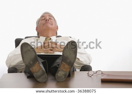 Businessman resting in with shoes on desk