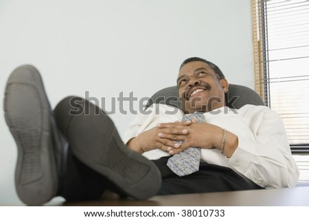 Businessman resting on a chair and smiling.