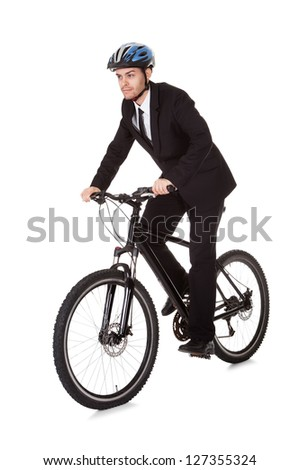 Businessman riding a bicycle to work in his suit exercising for fitness and health and to save on carbon emissions