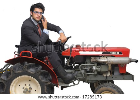 Businessman riding a tractor with cellphone, against a white background