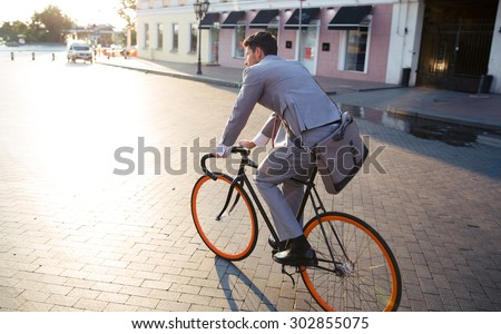Businessman riding bicycle to work on urban street in morning