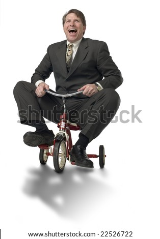 Businessman riding child's tricycle