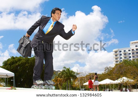 Businessman rollerblading with briefcase in urgency at park. Horizontal shot.