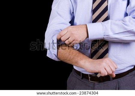 businessman rolling his sleeves ready to work (isolated on black)