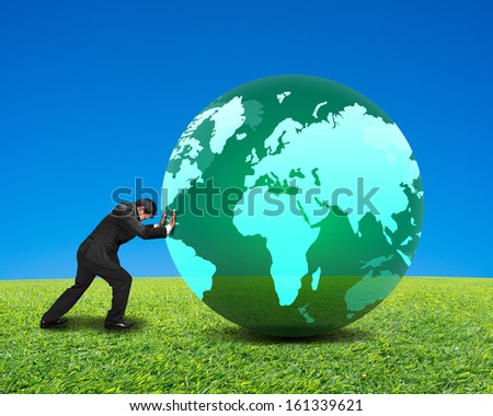 businessman rolling large green ball with global map on it with green meadow and clear blue sky background