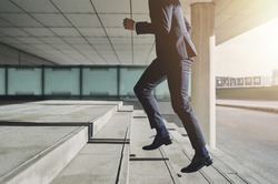 Businessman running fast upstairs. Horizontal outdoors shot.