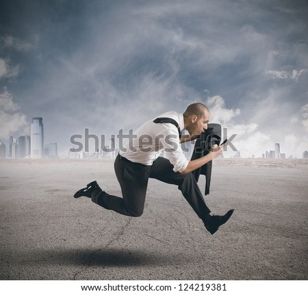 Businessman running with mobile phone in hand