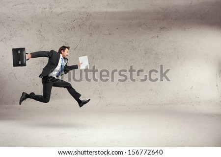 businessman running with some papers in his hand