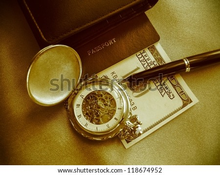 Businessman's accessories including pocket watch, pen, wallet, passport and money.