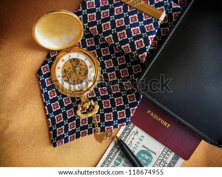 Businessman's accessories including pocket watch, pen, wallet, passport, money, stickpin and necktie.