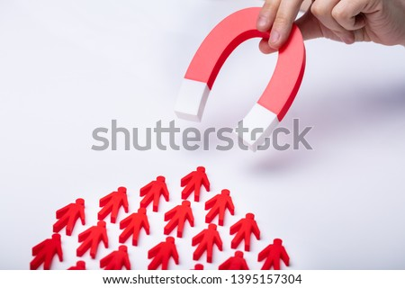 Businessman's Hand Attracting Red Team With Horseshoe Magnet On White Background #1395157304