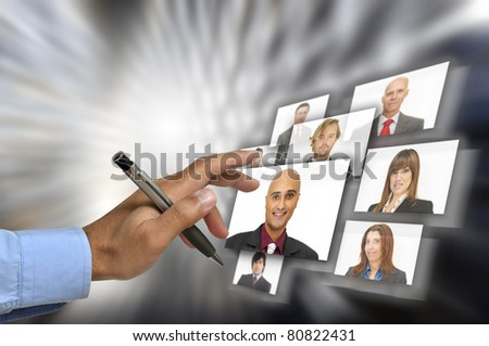 Businessman's hand choosing employees with modern technology - stock photo