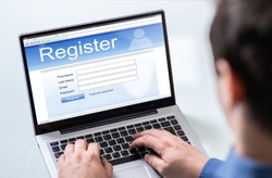 Businessman's Hand Filling Online Registration Form On Laptop