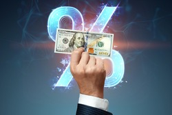 Businessman's hand holding a hundred dollar bill and percent on the background. The concept of salary, investment, donation, dividend