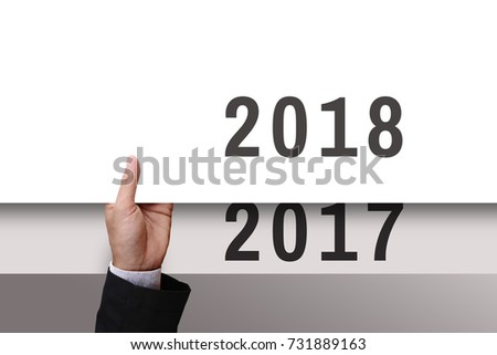 Businessman's hand holding from under of white cardboard or paper new year 2018 replace old year 2017. #731889163