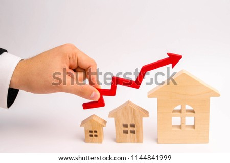 businessman's hand holds the red arrow up above the houses. The concept of growth in demand for real estate. Increase in the value of property, capital appreciation and liquidity. economic growth.