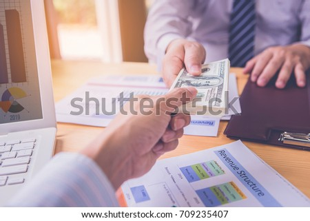 Businessman's hand is giving money for partner. investment concept #709235407
