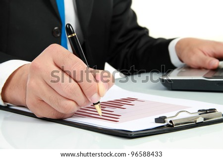 Businessman's hand looking at diagram on financial report - stock photo