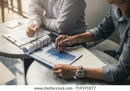 Businessman's hand pointing at business document during discussion at meeting. #759591877