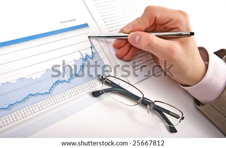Businessman's hand showing diagram on financial report with pen. Business background