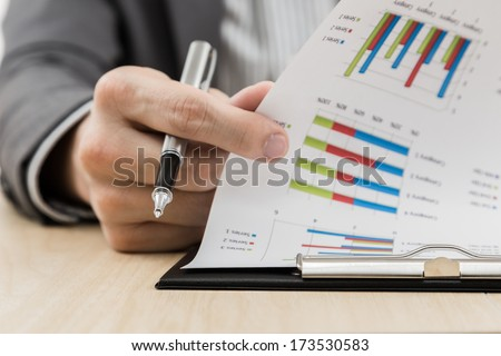 Businessman\'s hand showing financial report on table