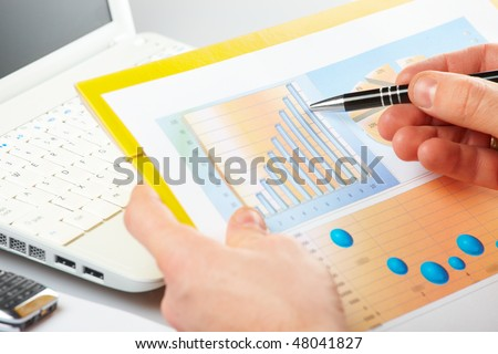 Businessman's hand showing graph on financial sells or popularity report with pen