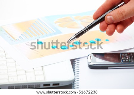 Businessman's hand showing graph on financial sells or popularity report with pen.