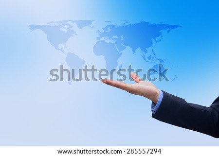 Businessman\'s hand showing map of the world on blurred blue sky, selective focused.business concept