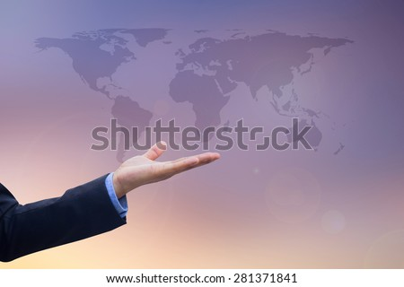 Businessman\'s hand showing map of the world on blurred twilight sky, selective focused.business concept
