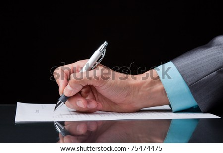 businessman's hand with pen on the table over black background