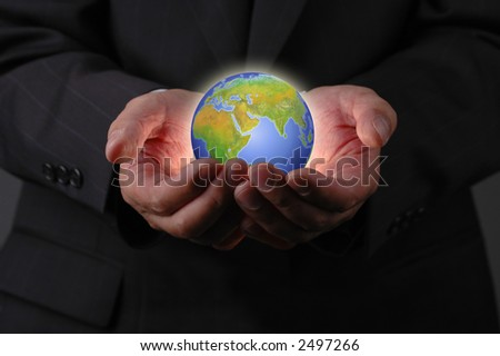 Businessman's hands and earth on dark background - stock photo