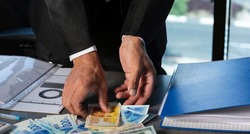 Businessman's Hands holding a fan of money of Israeli New Shekels. Stack of Money scattered (Currency of usa dollar, nis banknotes) on the table. Cropped image of Hand holds banknotes. Selective focus