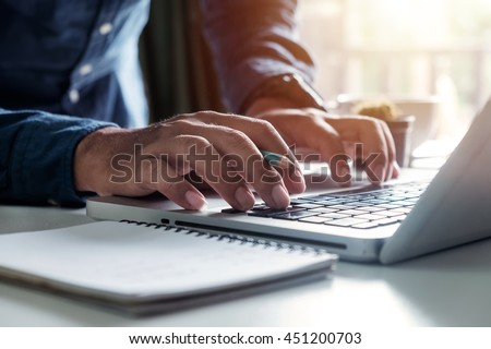 Businessman s hands typing on laptop keyboard in morning light (computer, typing, online) #451200703