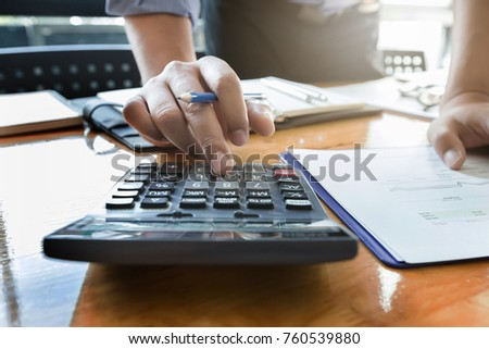 Businessman's hands using calculator and Financial data analyzing on wooden desk at the office