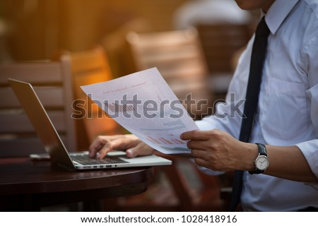 BUsinessman's Key Research And AUDIT Income Statement DATA from Excel Spreadsheets.Audit Making Database Report Financial Planning Report In a CAFE in Park Near the Office before Entering Meeting #1028418916