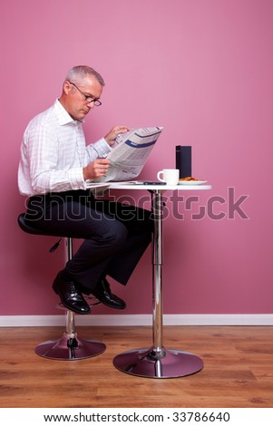 Businessman sat in a cafe reading the morning news, the newspaper has had any copyright issues removed and the text is unreadable. The menu is blank also.