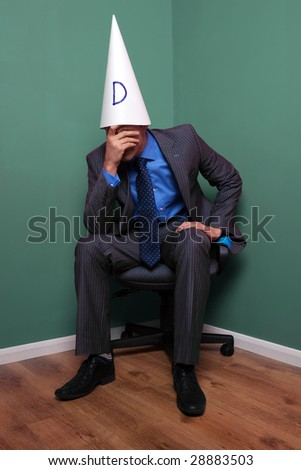 Businessman sat on a chair in the corner wearing a dunce hat