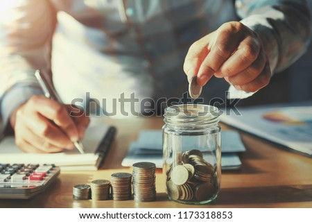 businessman saving money concept. hand holding coins putting in jug glass #1173318853