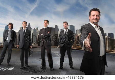 Businessman saying welcome with his team on the background