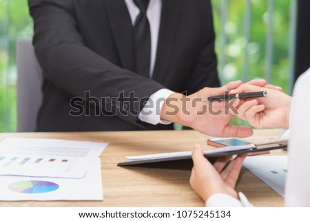 Businessman says no or hold on when woman giving pen for signing a contract. #1075245134