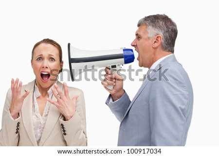 Businessman screaming after his colleague with a megaphone against white background