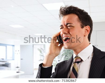 Businessman screaming at the phone. Office in the background.