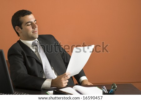 Businessman seated at desk looking at paperwork. Horizontally framed photo.