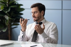 Businessman seated at workplace desk holding smart phone speaking through microphone sending voice message, solving issues distantly. Business, instant communication, modern tech easy usage concept