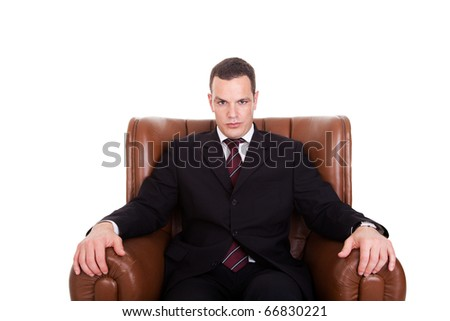 Businessman seated on a chair, isolated on white background. Studio shot.