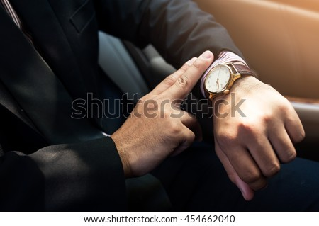 Businessman seats on the car and looking at watch ,business concept ,vintage tone