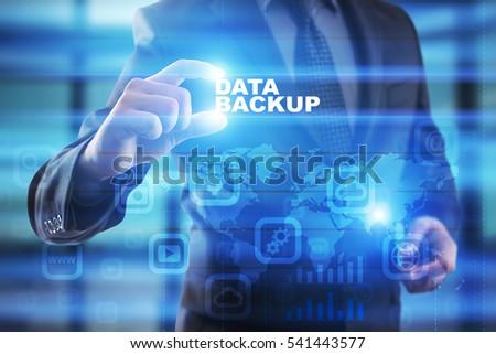 Businessman selecting data backup on virtual screen. #541443577