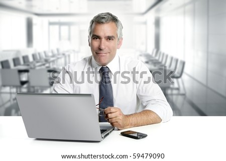 businessman senior gray hair working laptop interior modern white office
