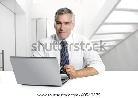 businessman senior gray hair working laptop interior modern white office [Photo Illustration] - stock photo